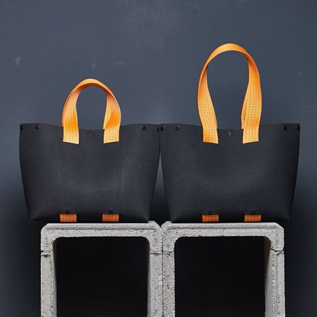Two EvaTwo black tote bags side by side with different length orange straps by Lommer Design