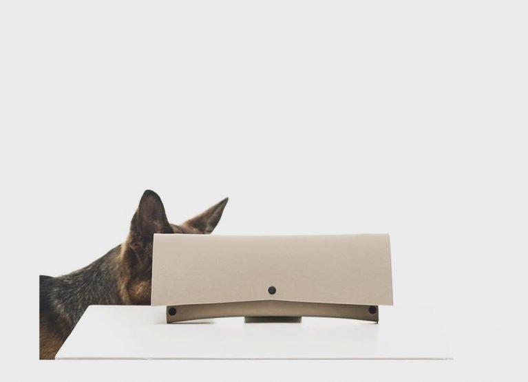 A dog hiding behind EvaClutch, a clutch bag by Lommer Design