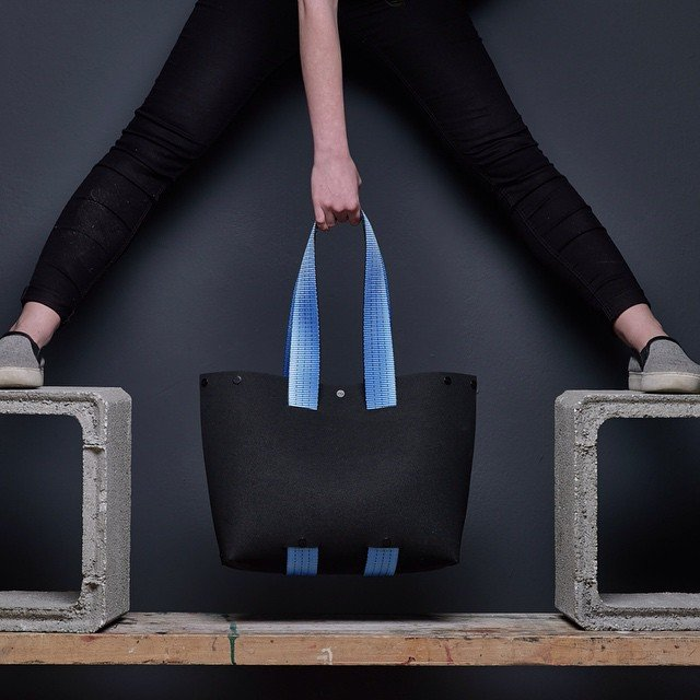 EvaTwo Black Tote Bag by Lommer Design held between a girl's legs